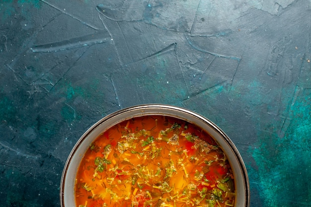 Top view delicious vegetable soup inside plate on a dark green background food vegetables ingredients soup product meal