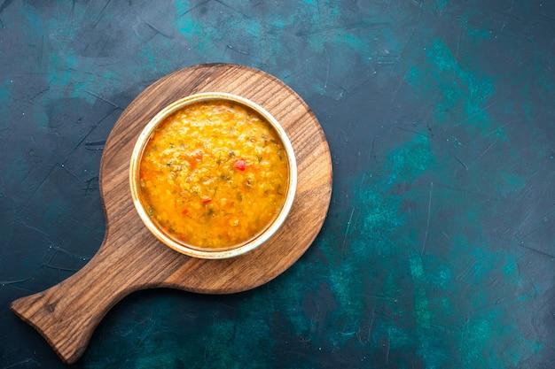 진한 파란색 책상에 둥근 접시 안에 맛있는 야채 수프를 봅니다.