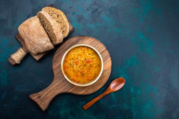 Vista dall'alto una deliziosa zuppa di verdure all'interno del piatto rotondo con pane sulla scrivania blu scuro.