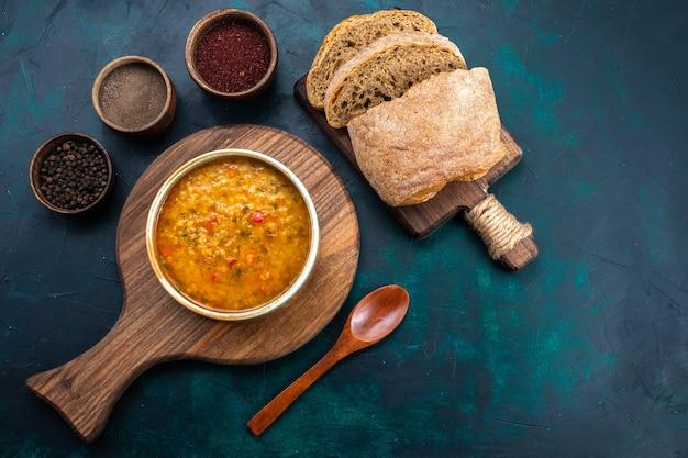 Vista dall'alto una deliziosa zuppa di verdure all'interno del piatto rotondo con pane e condimenti sulla scrivania blu scuro.