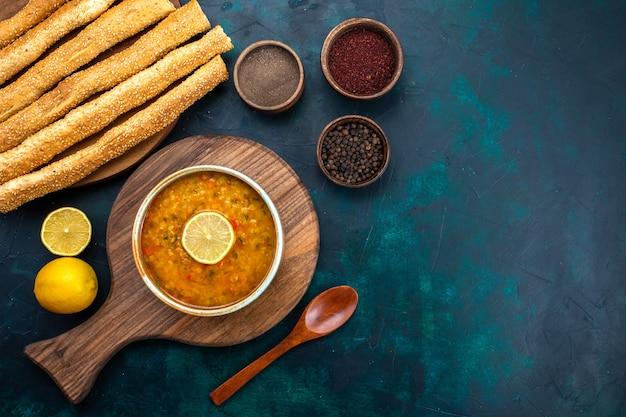 Вид сверху вкусный овощной суп внутри круглой тарелки с приправой лимоном и хлебом на темно-синем столе.