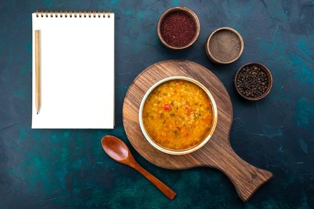 Вид сверху вкусный овощной суп внутри круглой тарелки с приправами на темно-синем столе.