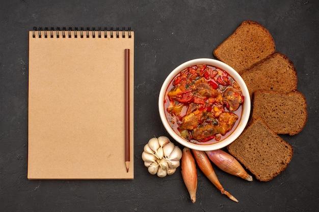 어두운 공간에 어두운 빵 덩어리와 상위 뷰 맛있는 야채 수프