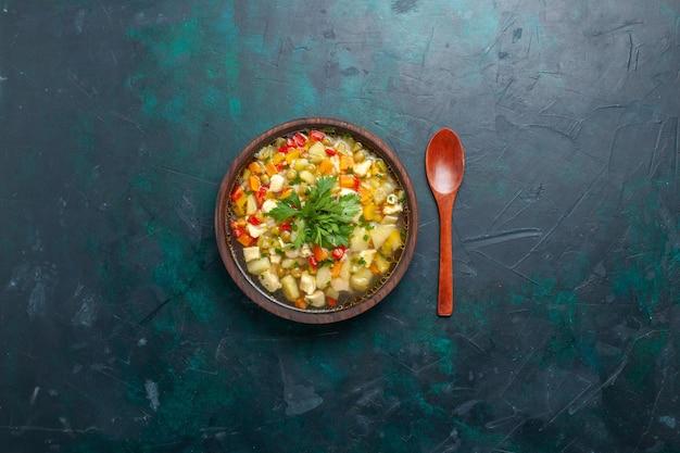 Vista dall'alto una deliziosa zuppa di verdure con diversi ingredienti all'interno della piastra marrone sul piatto di cibo caldo di cibo di zuppa di verdure di zuppa di scrivania scura