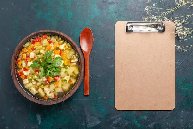 Vista dall'alto una deliziosa zuppa di verdure con diversi ingredienti e blocco note sul pasto di cibo caldo di minestra di verdure della scrivania scura