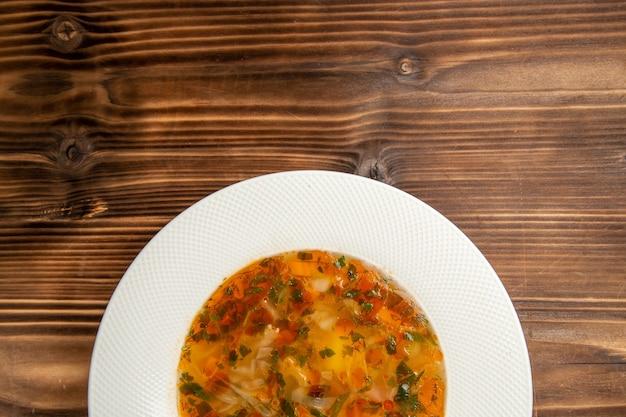 Vista dall'alto una deliziosa zuppa di verdure con verdure sul condimento di farina di verdure minestra tavolo in legno marrone