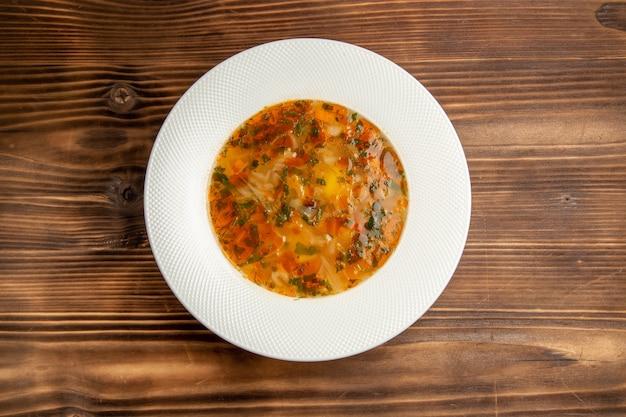 Вид сверху вкусный овощной суп с зеленью на коричневом деревянном столе суп еда овощная еда приправа