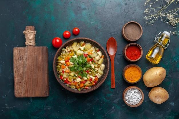 Vista dall'alto deliziosa zuppa di verdure con olio d'oliva e diversi condimenti su sfondo blu scuro ingrediente zuppa di verdure olio per insalata