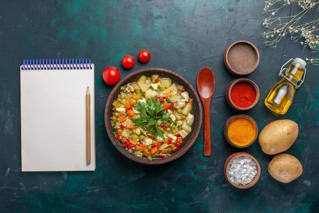 トップビューオリーブオイルのメモ帳と暗い背景の材料にさまざまな調味料を使ったおいしい野菜スープ野菜スープサラダオイル