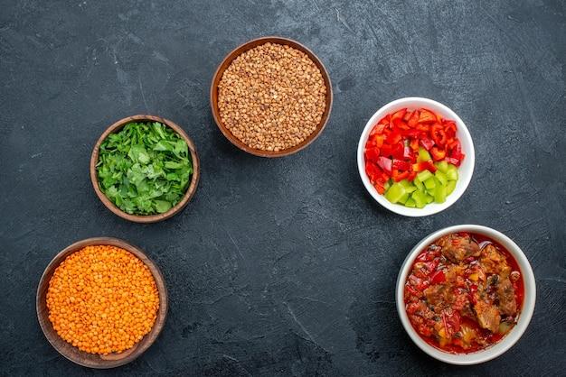 Вид сверху вкусный овощной суп с сырой гречкой и зеленью на сером пространстве