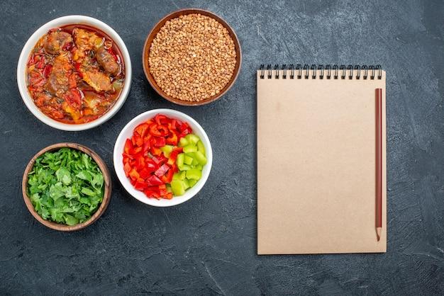 Vista dall'alto deliziosa zuppa di verdure con grano saraceno crudo e verdure sulla scrivania grigia