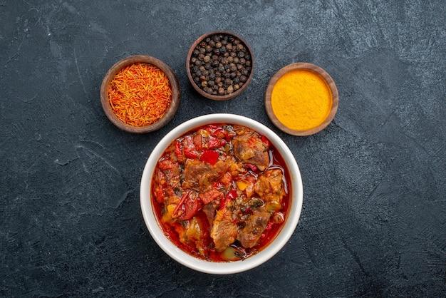 灰色の空間に調味料を入れたトップビューのおいしい野菜スープ