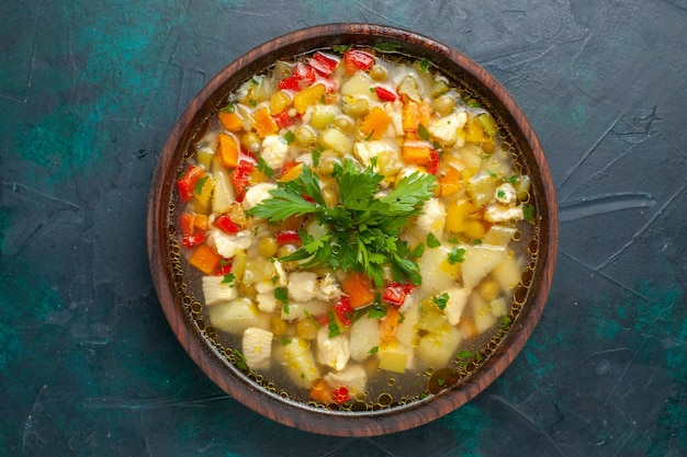 Top view delicious vegetable soup with sliced vegetables and greens on dark-blue surface soup vegetable food meal hot food dinner sauce