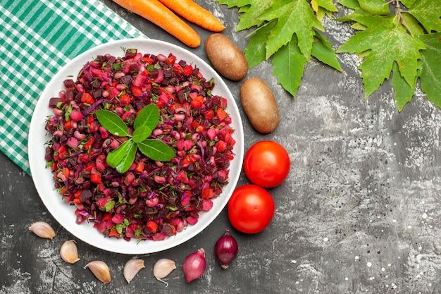 Vista dall'alto deliziosa insalata di barbabietole vinaigrette con verdure sulla superficie grigia