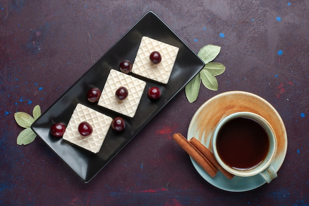 Top view of delicious waffles with cherries inside plate with tea on the dark surface