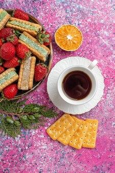 Vista dall'alto di deliziose cialde con tazza di tè e fragole rosse fresche sulla superficie rosa