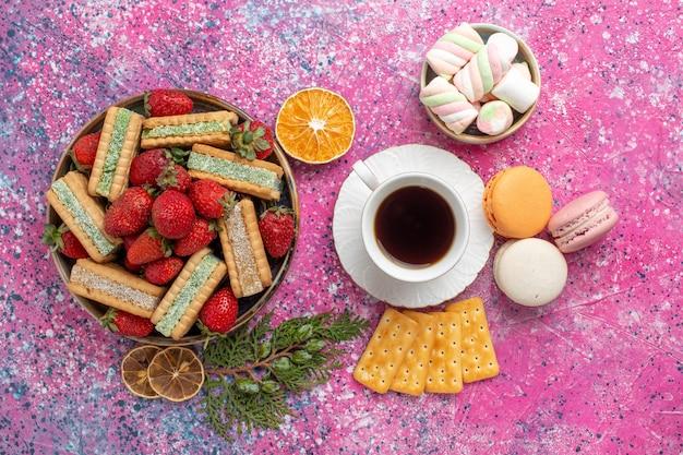 Vista dall'alto di deliziose cialde con tazza di tè macarons e fragole rosse fresche sulla superficie rosa
