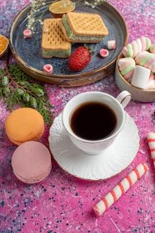 Vista dall'alto di deliziosi waffle con tazza di tè macarons e marshmallow sulla superficie rosa