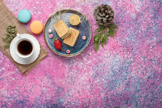 Vista dall'alto di deliziose cialde con tazza di tè e macarons sulla superficie rosa