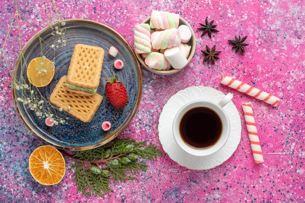 Top view of delicious waffles with cup of tea and marshmallow on pink desk