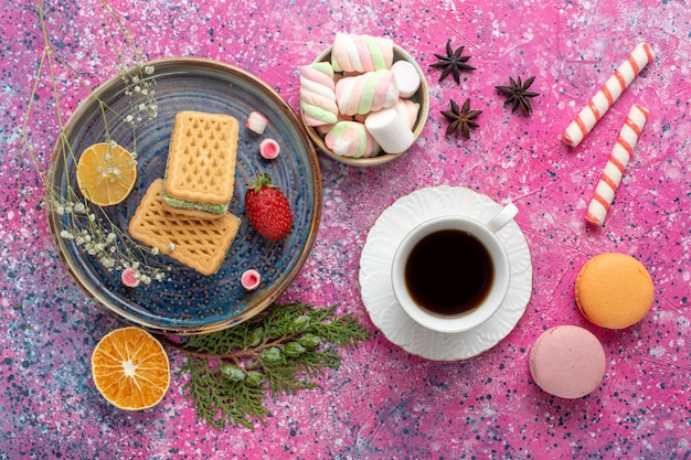 Top view of delicious waffles with cup of tea and marshmallow on pink surface