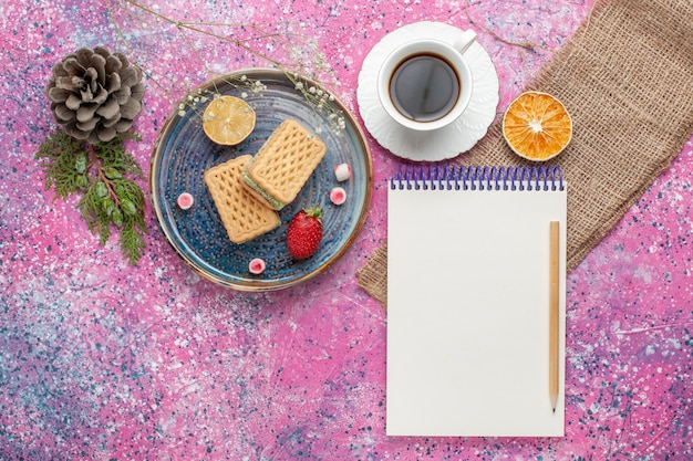 Top view of delicious waffles with cup of tea on pink surface