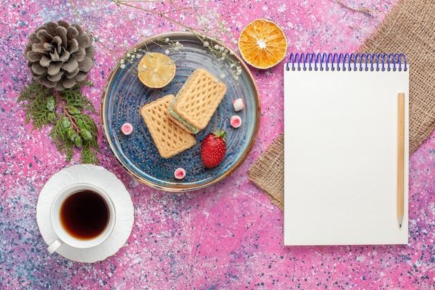 Vista dall'alto di deliziose cialde con tazza di tè sulla superficie rosa