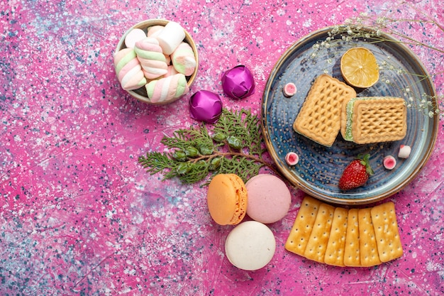 Top view of delicious waffles with french macarons and crackers on pink surface