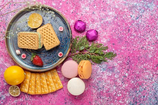 Vista dall'alto di deliziosi waffle con macarons francesi e cracker sulla superficie rosa