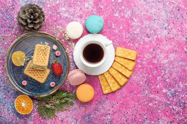 Top view of delicious waffles with french macarons crackers and tea on pink surface