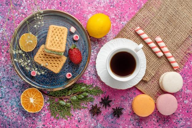 Vista dall'alto di deliziosi waffle con macarons francesi sulla superficie rosa chiaro