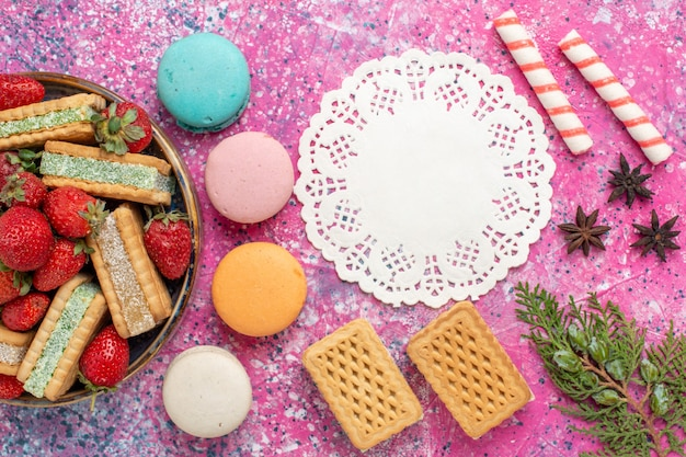 Top view of delicious waffles with french macarons and marshmallows on the pink surface