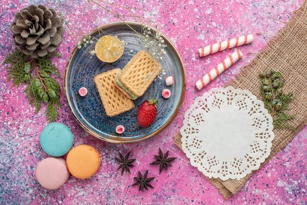 Vista dall'alto di deliziosi waffle con macarons francesi sulla scrivania rosa