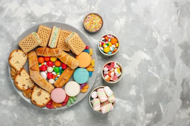 Vista dall'alto di deliziose cialde con fette di torta di macarons e caramelle sulla superficie bianca chiara