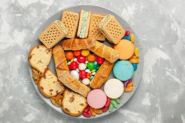 Vista dall'alto di deliziose cialde con fette di torta di macarons e caramelle sulla scrivania bianca