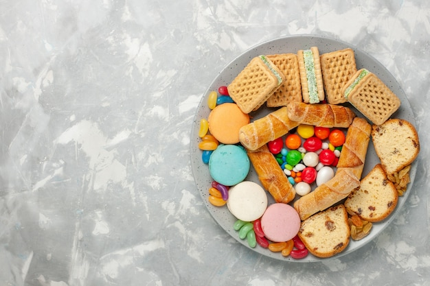 Top view of delicious waffles with macarons cake slices and candies on white surface
