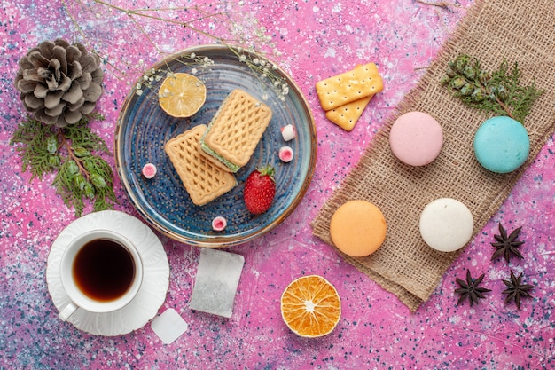 Top view of delicious waffles with macarons and cup of tea on pink surface