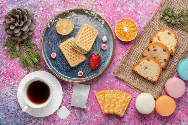 Top view of delicious waffles with macarons and cup of tea on the pink surface
