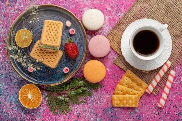 Vista dall'alto di deliziosi waffle con tè macarons e marshmallow sulla superficie rosa chiaro