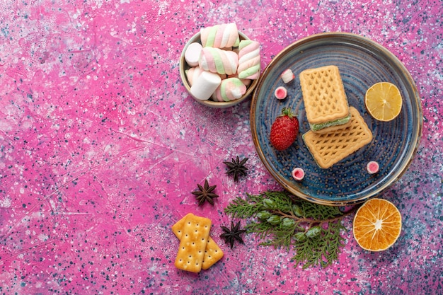 Top view of delicious waffles with marshmallow on pink surface