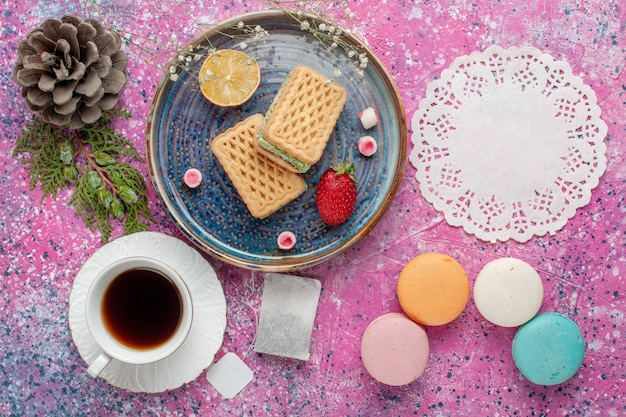 Top view of delicious waffles with yummy french macarons and tea on the pink surface