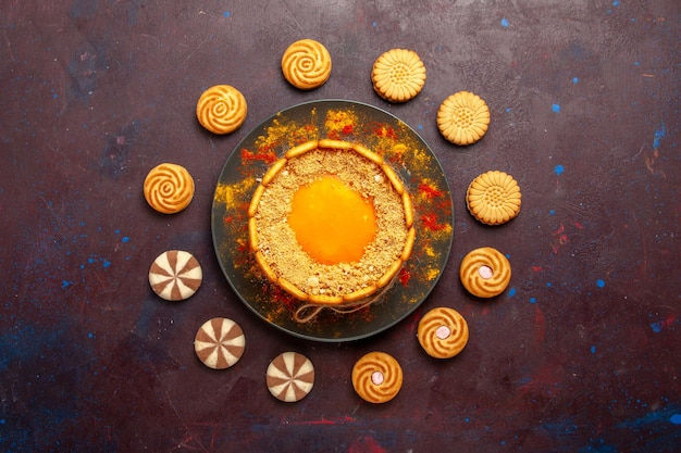 Top view delicious yellow cake creamy dessert with cookies on dark surface