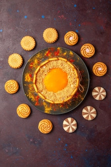 Top view delicious yellow cake creamy dessert with cookies on the dark surface