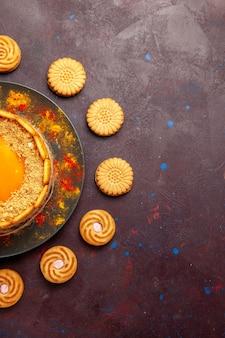 어두운 책상에 쿠키가 있는 맛있는 노란색 케이크 크림 디저트