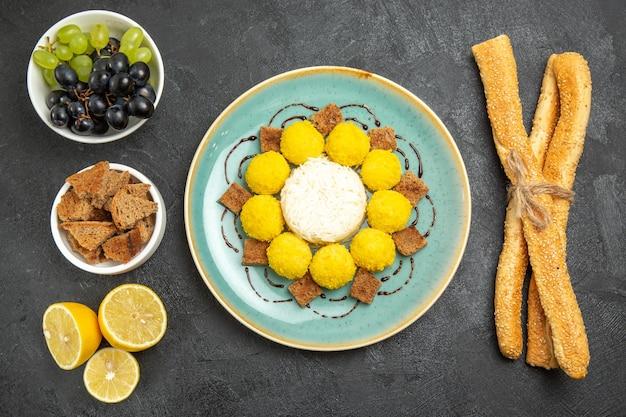 어두운 배경에 케이크 포도와 빵을 넣은 맛있는 노란색 사탕 설탕 과일 사탕 차 케이크 달콤한