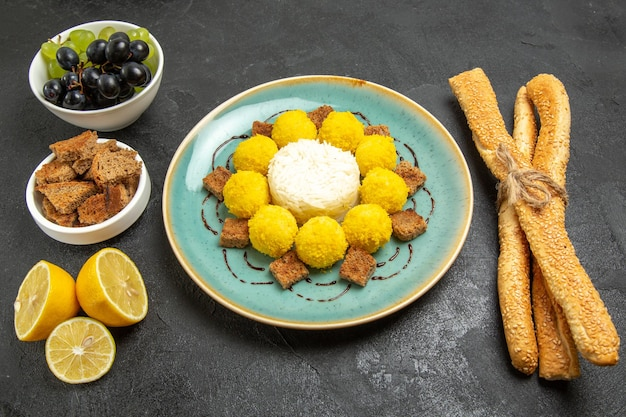 Top view delicious yellow candies with cake grapes and bread on a dark background sugar fruit candy tea cake sweet