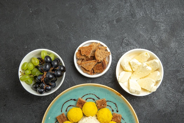Top view delicious yellow candies with cake grapes and cheese on dark grey background sugar fruit candy tea cake sweet