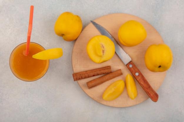 Vista dall'alto di deliziose pesche gialle su una tavola da cucina in legno con bastoncini di cannella con coltello con succo di pesca fresco su un bicchiere su sfondo bianco