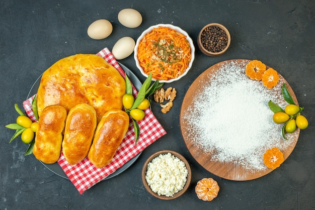 Top view of delicous fresh baked pastries and cheese peppers eggs flour tangerines on the wooden cutting board salad on dark blackground