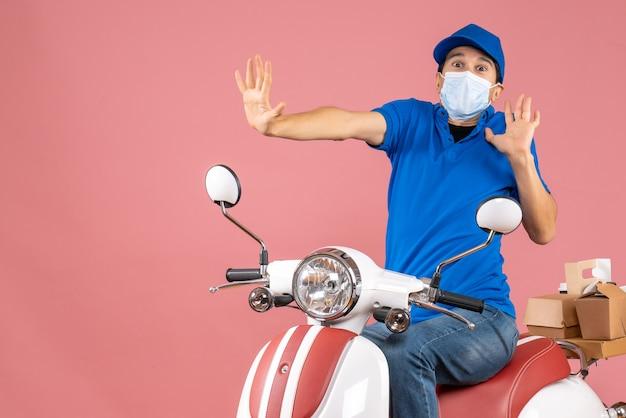 Vista dall'alto del ragazzo delle consegne in maschera medica che indossa un cappello seduto su uno scooter e si sente spaventato su uno sfondo di pesca pastello